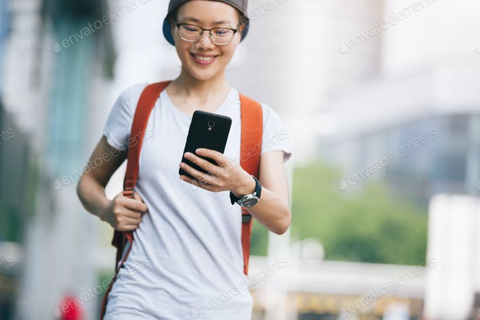 Asian woman use mobile phone on city street
