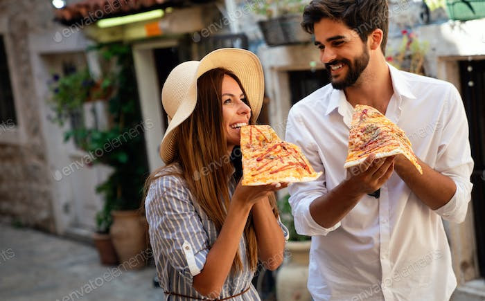 Group of friends eating pizza while traveling on vacation