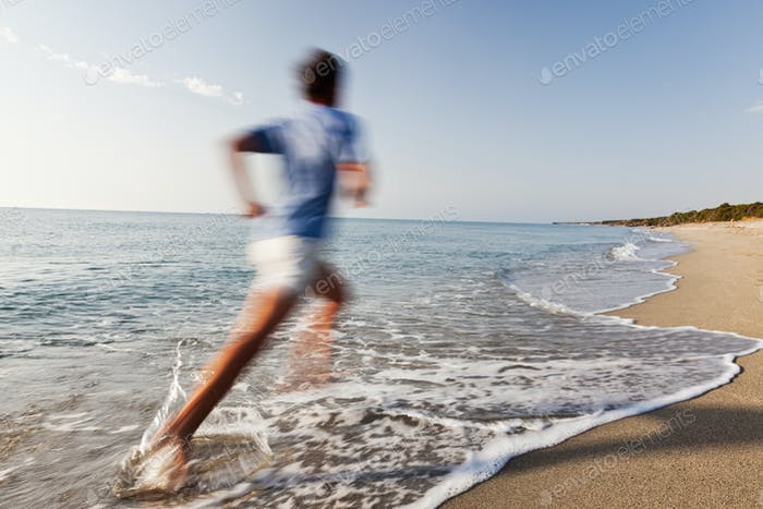 Young man running on a beach.