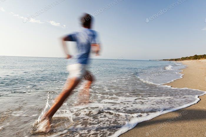 Junger Mann läuft an einem Strand.