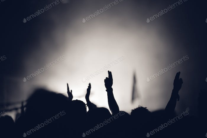 Cinematic desaturated silhouette of hands during festival