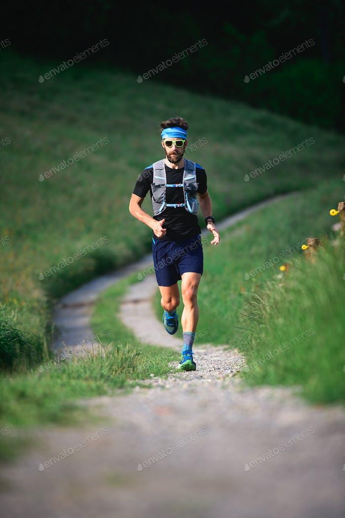Hombre con barba atleta corriendo en las montañas
