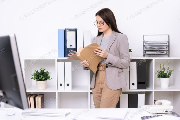 Contemporary young businesswoman or accountant looking through papers