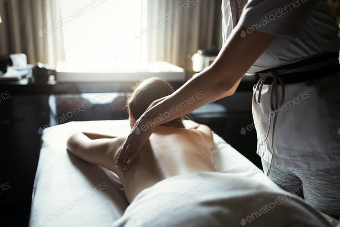 Beautiful young woman relaxing with massage treatment at beauty spa