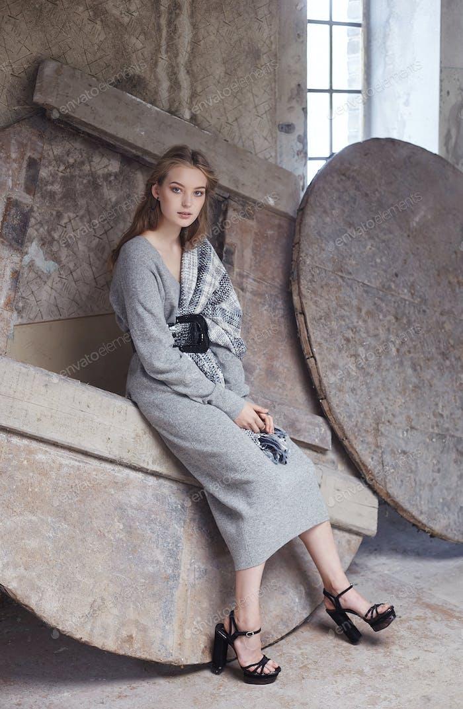 Blonde Frau in einem grauen Kleid.