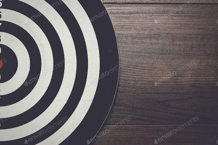 darts target on dark wooden background