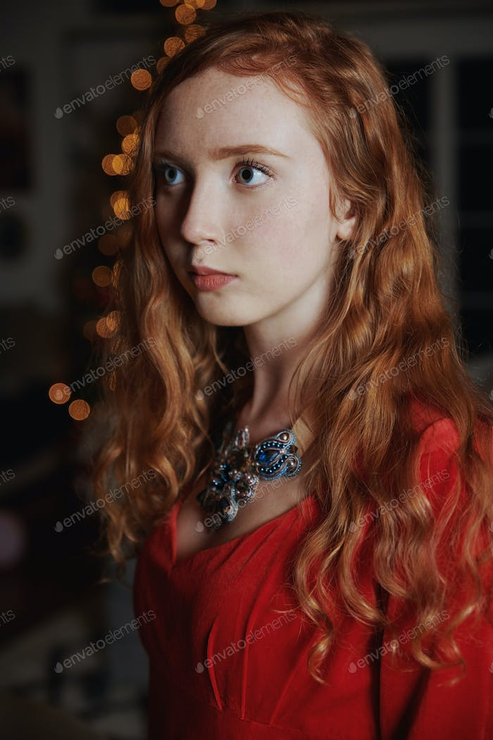 Redhead teenager in a red dress and an ornate necklace
