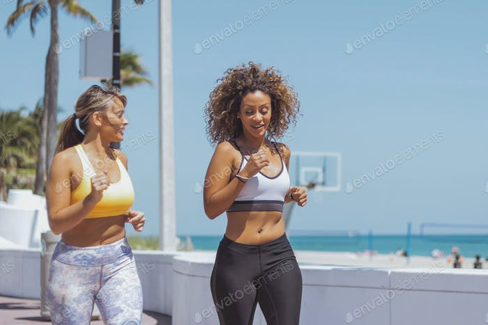 Content women jogging in tropical sunshine
