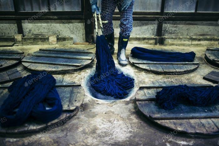 Close up of man beating indigo dye into strands of cotton.