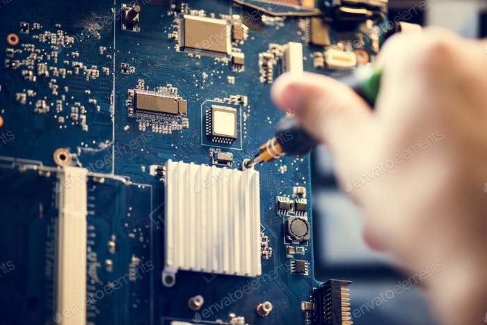 Closeup of hands with screwdriver over computer mainboard