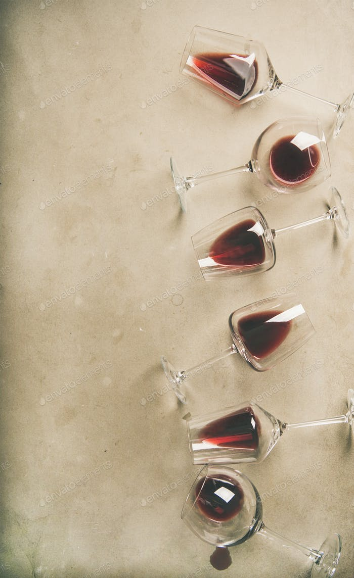 Red wine in glasses over grey concrete background, vertical composition