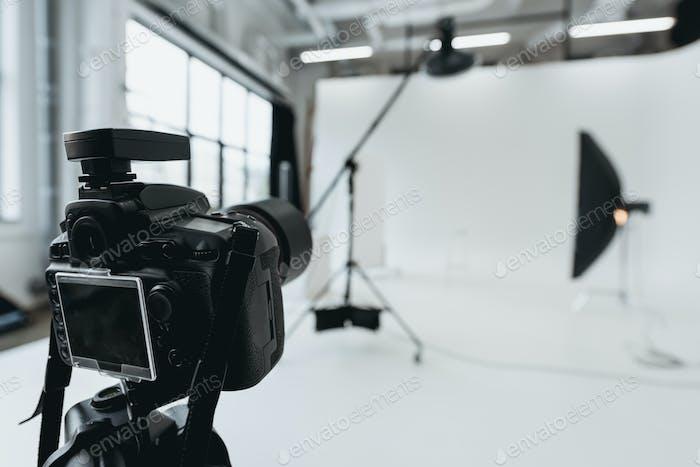 digital photo camera in photo studio with lighting equipment and softbox