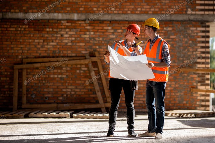 Structural engineer and architect dressed in orange work vests and helmets discuss documentation on