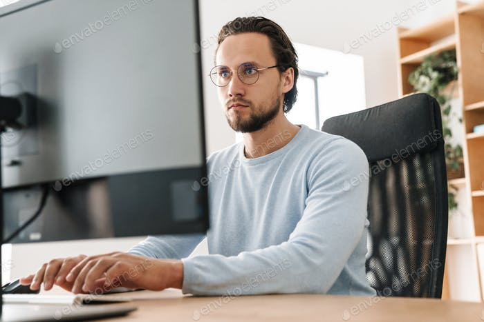 Image of focused unshaven programmer man working with computer