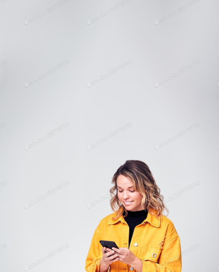Studio Shot Of Smiling Causally Dressed Young Woman Using Mobile Phone