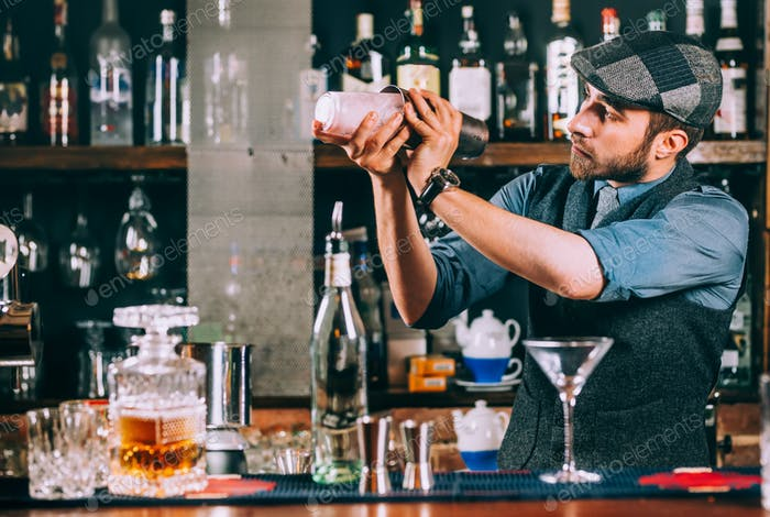 Porträt von Barmann, die Cocktails zubereitet, mit Shaker und Gießen von Getränken
