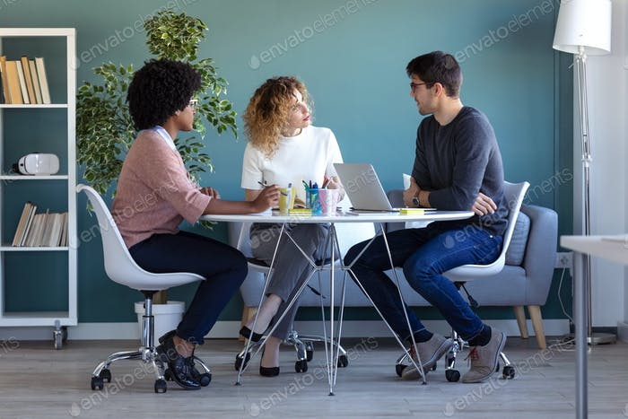 Casual young business people working and talking of they new project together in the office.