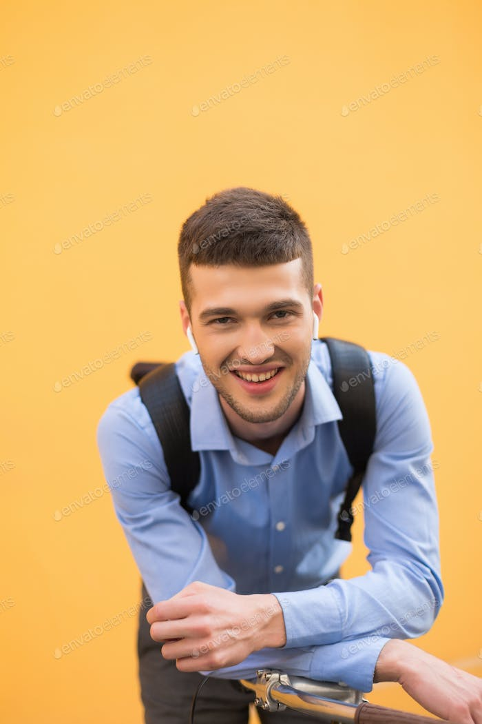 Young handsome smiling man in blue shirt and black backpack with