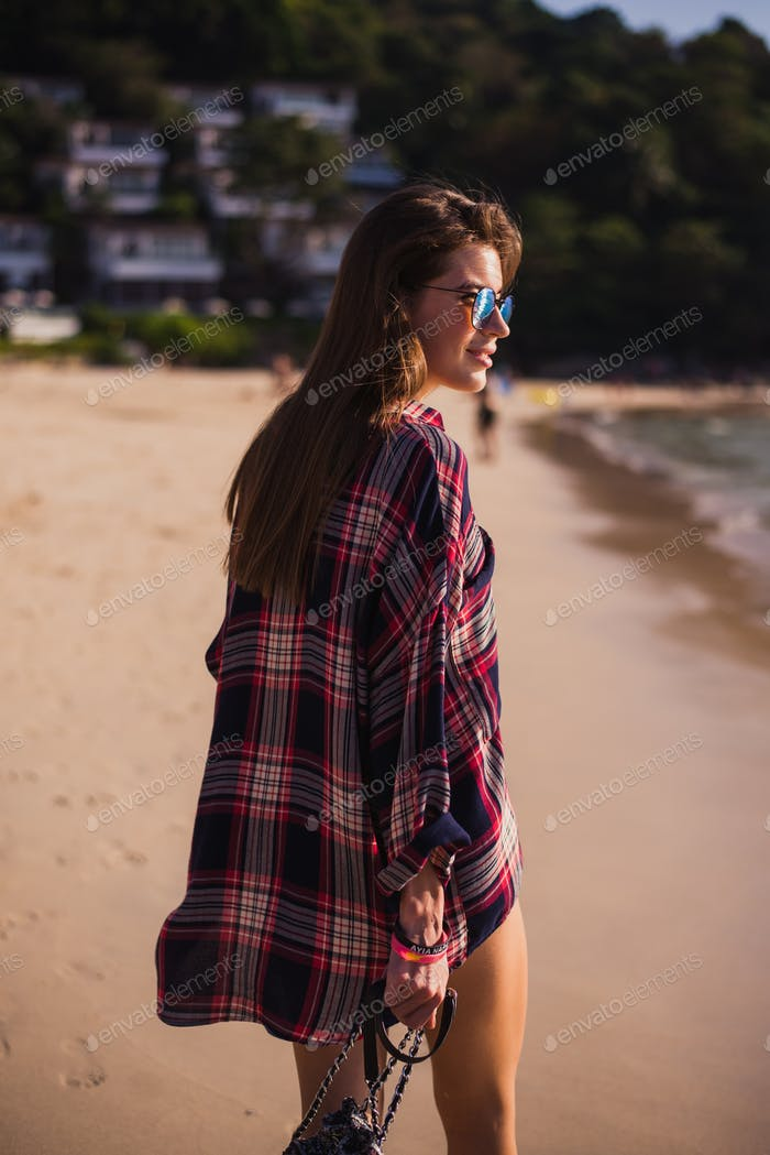 Summer lifestyle portrait of young pretty girl with sportive tanned body, walking to the beach of