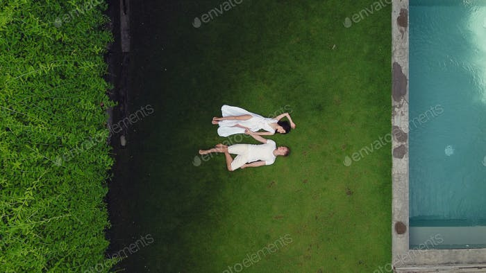 Couple lie on a graas on a Bali