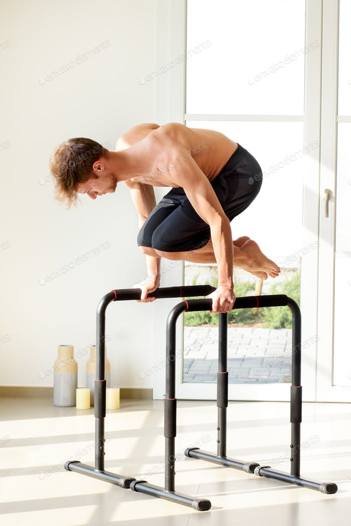 Man doing planche exercise on high bars