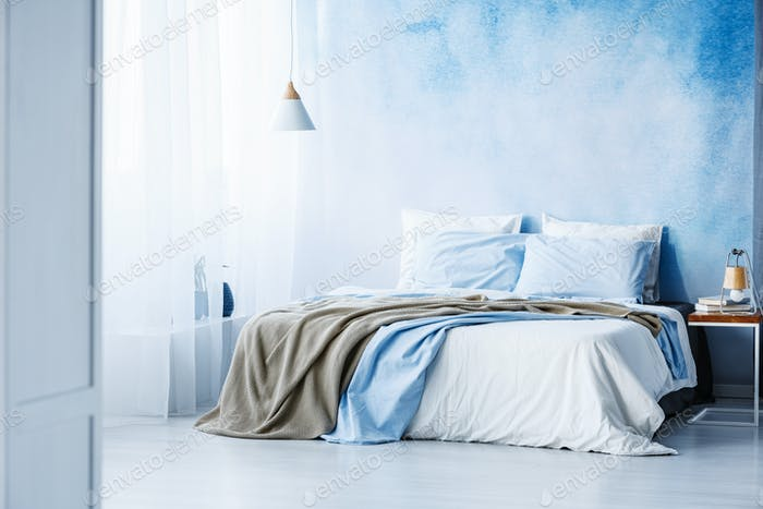 Yellow and blue bedding on white bed in minimal bedroom interior