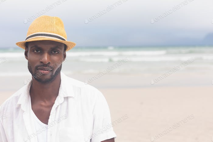 Portrait of handsome African American man standing at beach on a sunny day. He is looking at camera