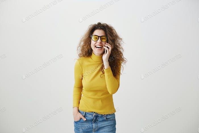 Fröhliche junge Frau im Gespräch auf Handy isoliert auf grauem Hintergrund
