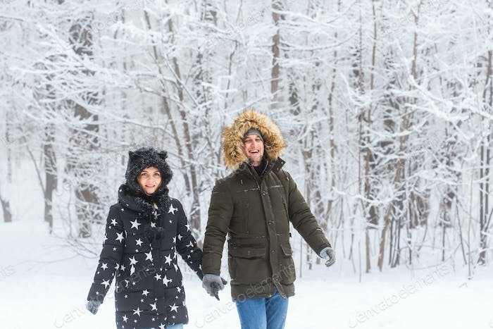 Young couple in love walks in the snowy forest. Active winter holidays