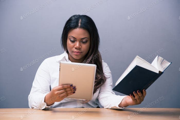Businesswoman choosing between e-book or paper book