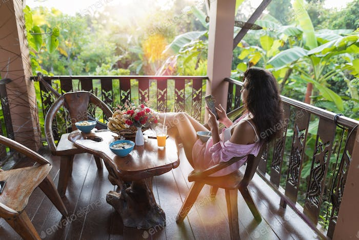 Young Woman Using Cell Smart Phone On Terrace Looking At Tropical Garden In Morning Beautiful Girl