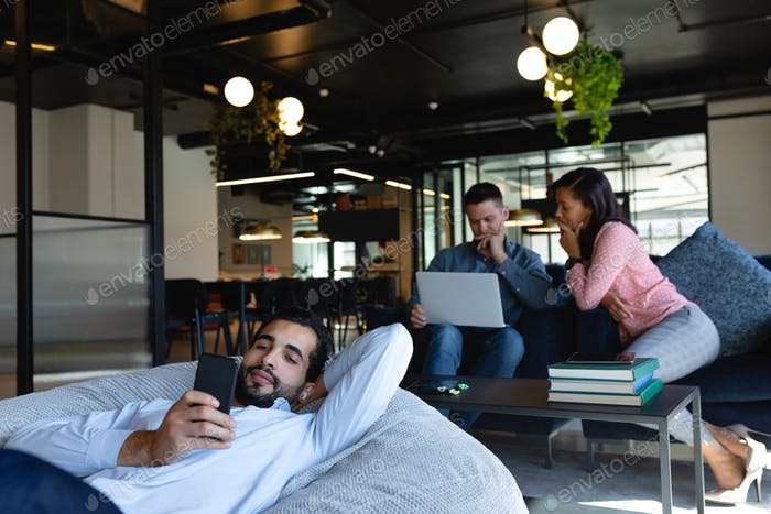 Caucasian man using his phone on a bean bag in a co working zone