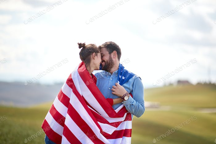 A couple cloaked by American flag at a meadow. Election, campaign, freedom concept