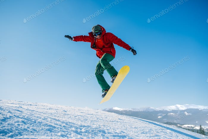 Snowboarder makes a jump on speed slope