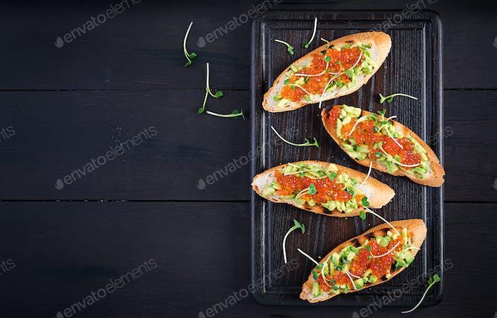 Sandwiches mit Lachs rotem Kaviar und Salsa mit Avocado. Sandwich zum Mittagessen.