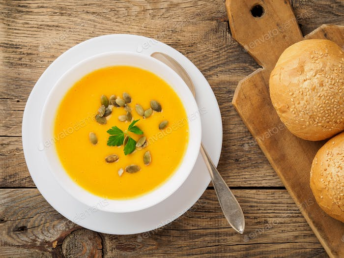 white bowl of pumpkin soup, garnished with parsley and sunflower seeds on wooden background