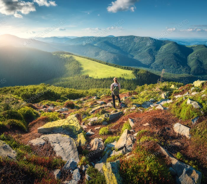 Mountains and standing young woman with backpack on the stones
