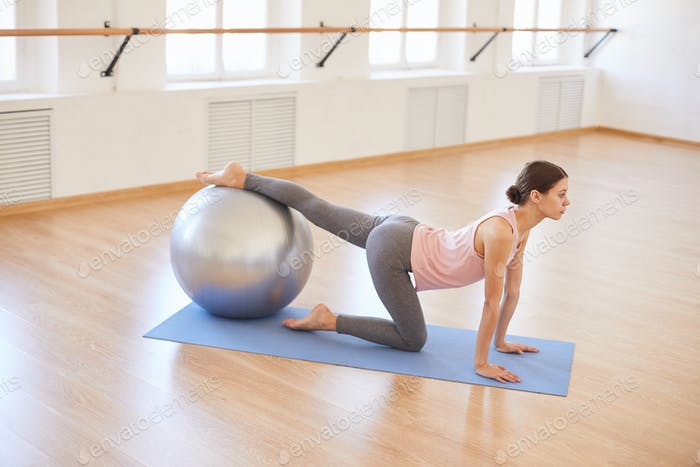 Slim girl practicing with exercise ball