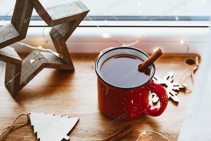 Schwarzer Tee mit Zimt in einem roten Becher