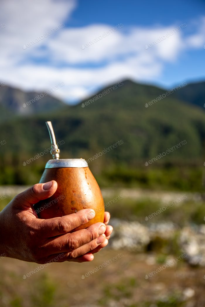Man holding calabash yerba mate in nature. Travel and adventure concept.