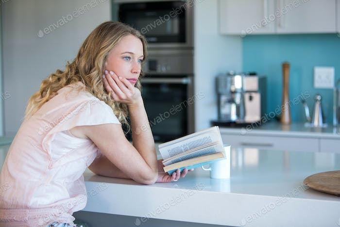 Pretty blonde reading a book at home in the kitchen
