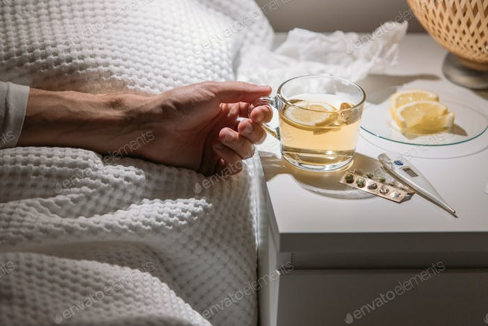 Male drinking hot beverage to get well from flu, fever and virus
