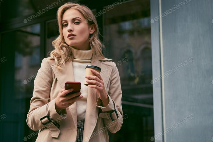 Beautiful blond girl in trench coat with coffee and cellphone confidently looking in camera outdoor