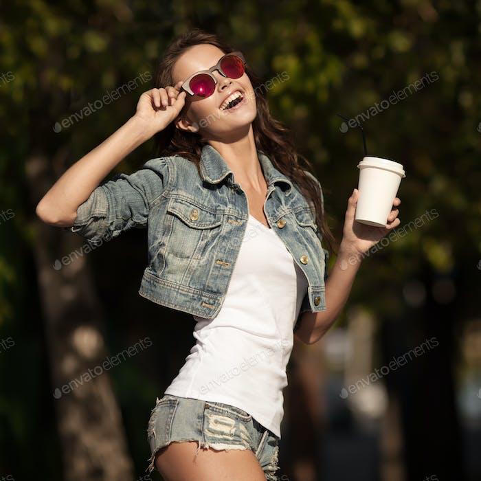 Junge lächelnde Frau trinken Kaffee zu gehen in einem Park.