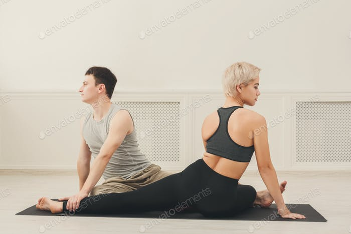 Young couple practicing yoga together in studio