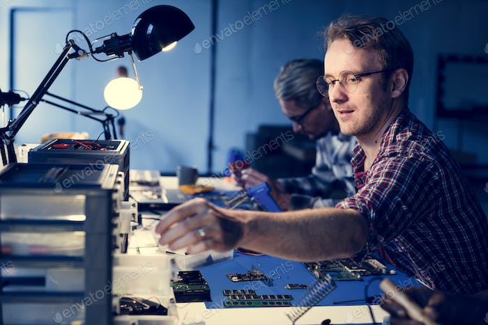 Technicians working on computer electronics parts