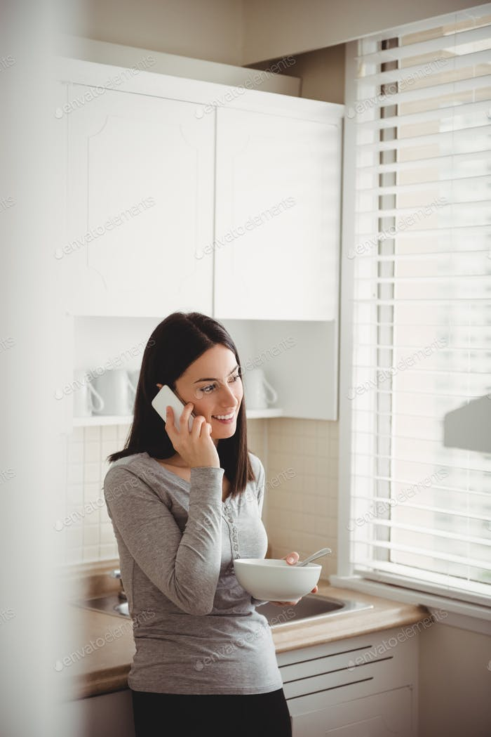 Woman talking on smart phone while holding food bowl