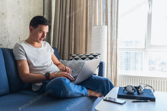 young attractive man sitting on sofa at home working on laptop online