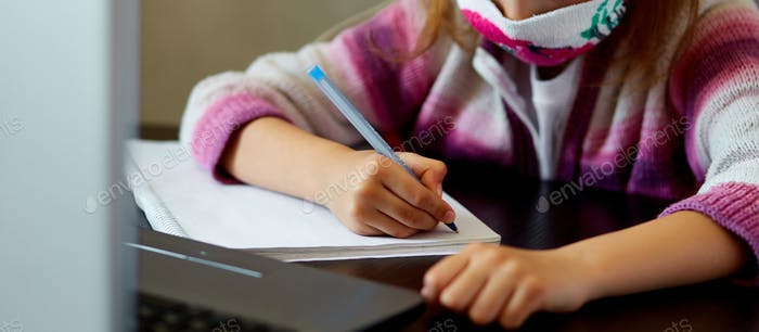 Schoolgirl studying at home with a notebook and doing school homework.