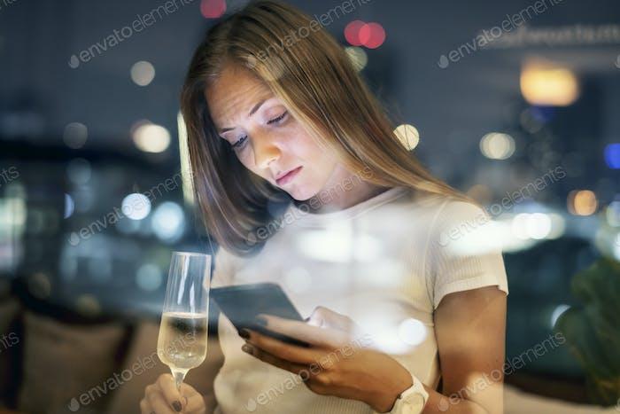 Ernsthafte junge Frau mit einem Smartphone an einer Dachterrasse Bar in der E
